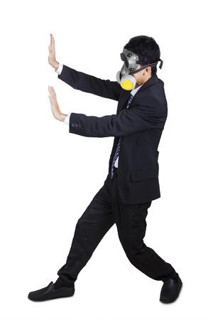 Businessman wearing a gas mask pushing something. Isolated on white background photo