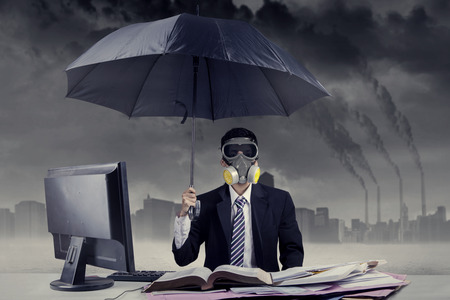 Businessman working in situation of air pollution by using a gas mask and an umbrella photo