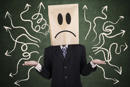 confused face: Confused businessman with paper head gesturing confuse Stock Photo