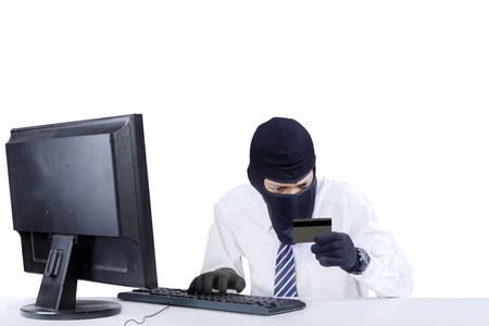 Internet Theft - businessman wearing a mask and holding a credit card while sat behind a computer photo