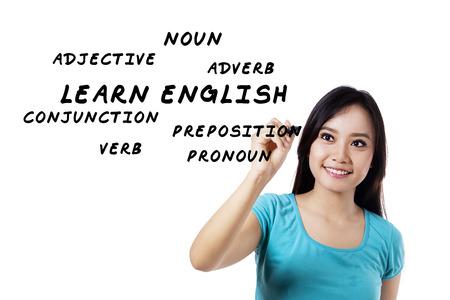 verb: Female student writes english language materials on whiteboard