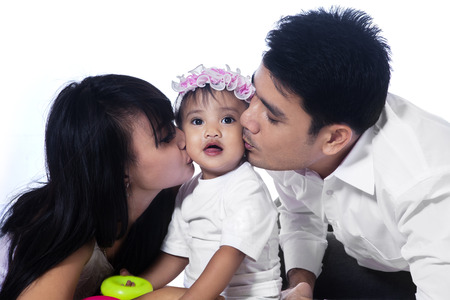 Happy family with Asian parents kissing their baby girl isolated over white photo