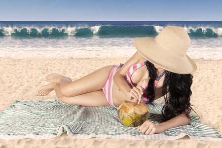 Beautiful woman drinking a coconut water on the beach photo