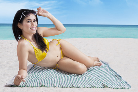 Portrait of smiling beautiful woman sunbathing on a beach photo