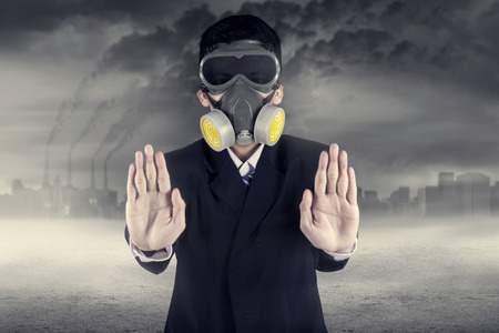 stop pollution: Pollution concept: portrait of businessman in a gas mask warn to stop pollution