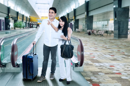 airport arrival: Young couple with suitcase standing at airport Stock Photo