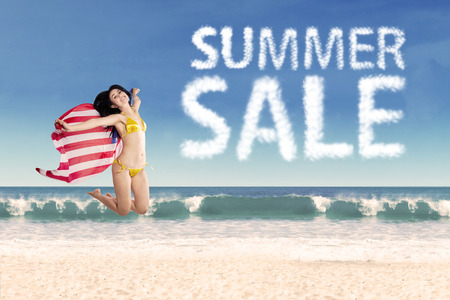 Summer sale clouds and woman jumping at beach photo