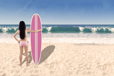 Rear view of beautiful young woman standing at beach with a surfboard photo