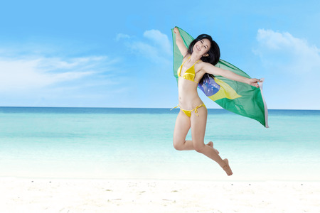 Portrait of Brazilian fans jumping at beach while holding Brazilian flag photo