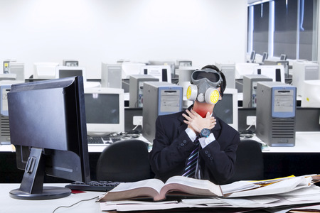 Businessman wearing a gas mask holding his neck photo