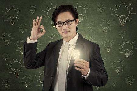Businessman holding lightbulb and showing thumb up symbolizing great idea