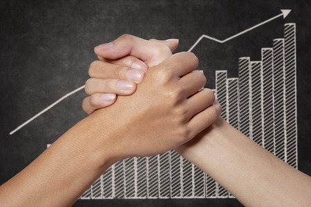 financial security: Businessman holding woman hands with growth graph on blackboard Stock Photo