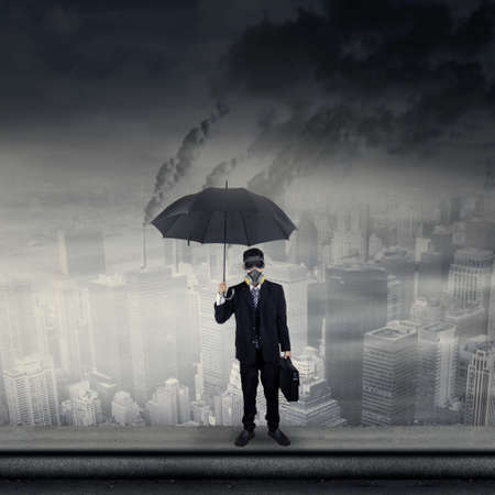 Businessman standing on a rooftop with polluted city scape in background photo