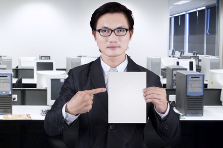 Businessman showing empty placard in the office photo