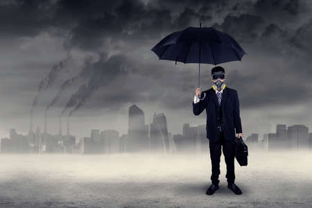 Businessman standing outdoors wearing a gas mask while holding an umbrella and briefcase photo