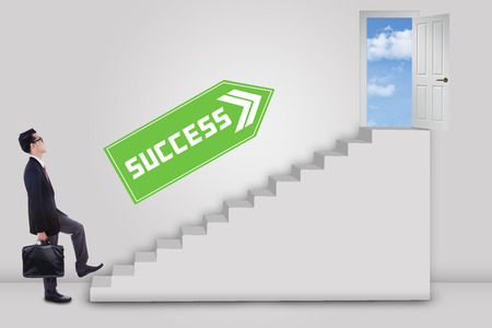 Businessman stepping up to the door of success with an arrow direction to the door photo