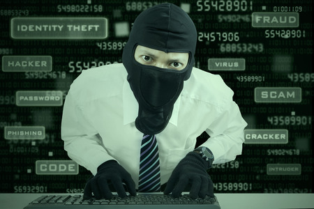 Computer hacker - businessman wearing mask stealing data from computer.  photo