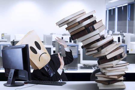 workaholic: Businessman overworked with a pile of books in the office Stock Photo