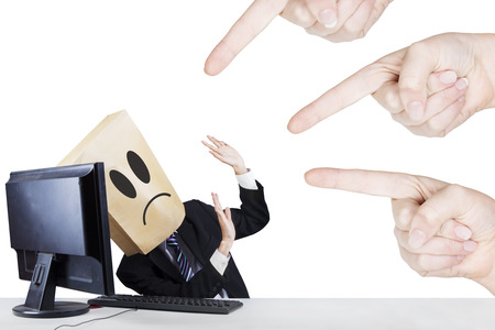 pasteboard: Businessman with carton head bullied by fingers. isolated on white background