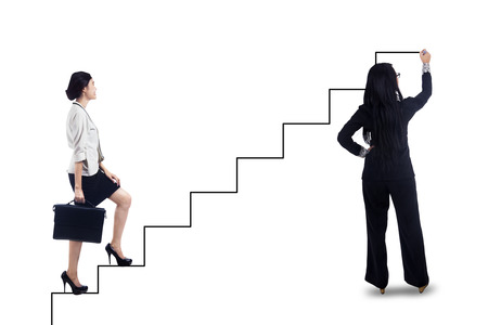 Businesswoman stepping up on stairs to gain her success with businesswoman drawing the stairs photo