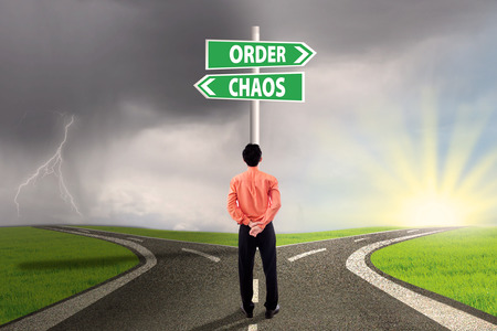 order chaos: Businessman standing on the road looking at signpost of order and chaos