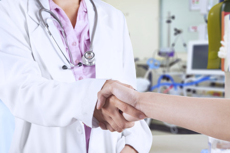 Doctor shakes hands with a patient at hospital photo