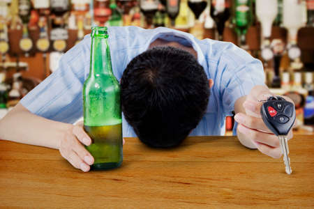 Drunk man sleeping on the table with beer bottle and car keys on his hand photo