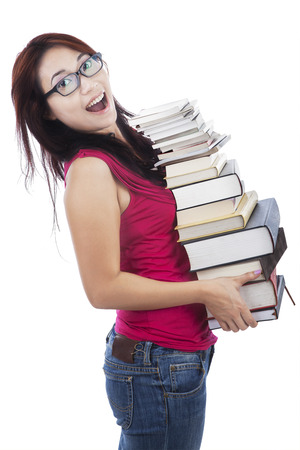 Attractive young female college student carrying a stack of books  shot in studio photo