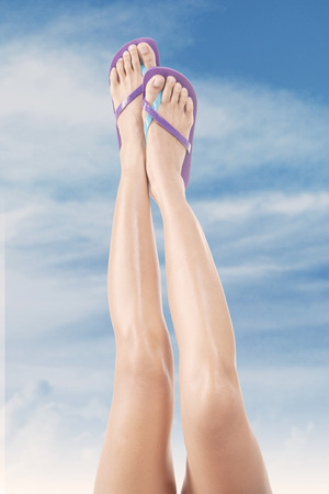 waxed: Beautiful female legs with flip-flops upward. Shoot outdoors at summertime