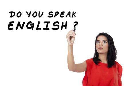 Learning language concept. Female student write Do You Speak English? photo