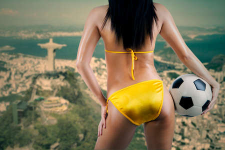Womans Sexy Backside Holding a Soccer Ball and looking at the city of rio de janeiro photo