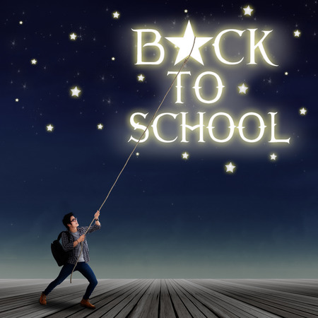 night school: Portrait of young male student pulling down a back to school text and the stars with rope