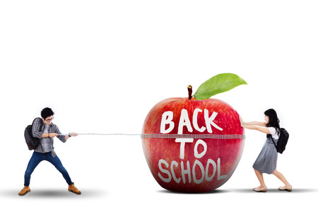 big apple: Back to school concept with students pulling and pushing a big apple
