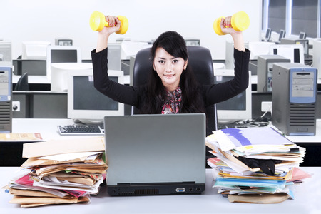 Business woman working and workout at her office photo
