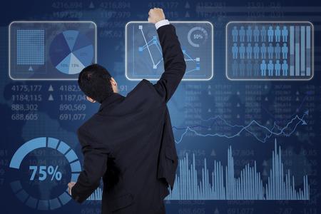 futuristic man: Successful businessman and financial graph on the futuristic screen