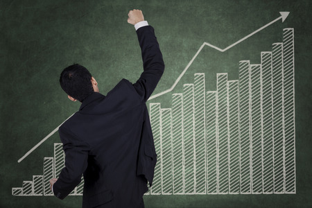 performance improvement: Successful businessman and financial graph on the wall