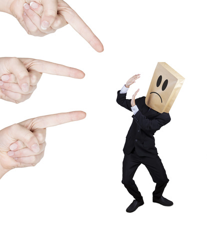 scolded: Worried businessman with cardboard head scolded by people Stock Photo