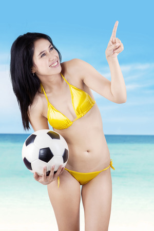 Portrait of sexy model with a ball pointing at copyspace photo