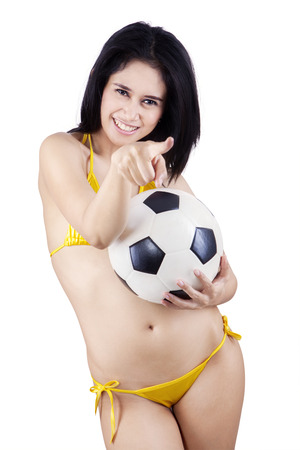 Young sexy woman with a soccer ball pointing at camera  photo