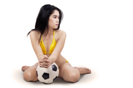 Portrait of sexy woman with soccer ball sitting on white background