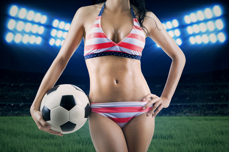 Sexy woman wearing striped bikini holding a soccer ball in field photo