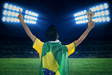 Backside of expressive brazilian player holding a trophy celebrating victory photo