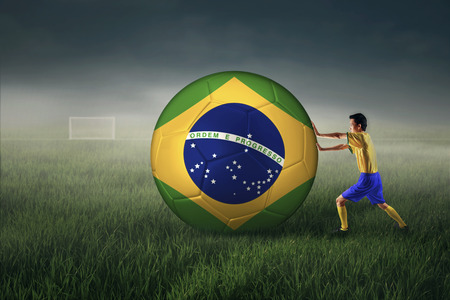Brazilian soccer player pushing a big soccer ball photo