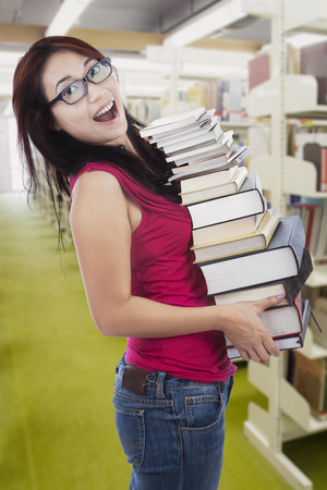 Attractive female student bring stack of books in the library photo