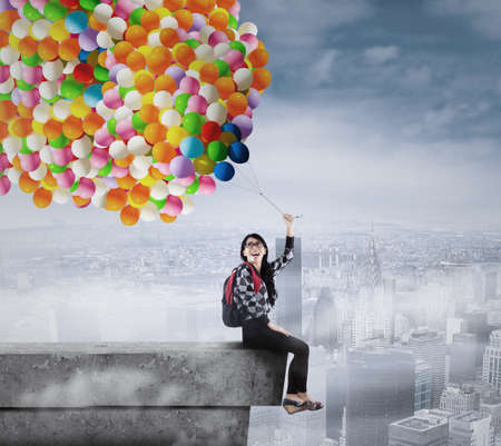 college building: Female student holding a bunch of balloons on the rooftop Stock Photo