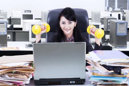 salud y deporte: Mujer de negocios de trabajo y entrenamiento en su oficina Foto de archivo