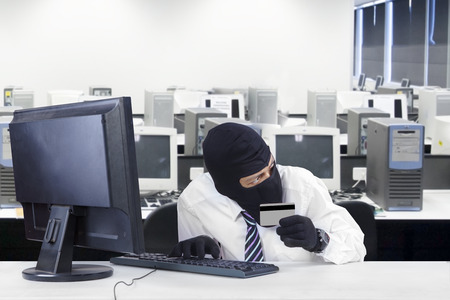 scammer: Internet Theft - businessman wearing a mask and holding a credit card while sat behind a computer Stock Photo
