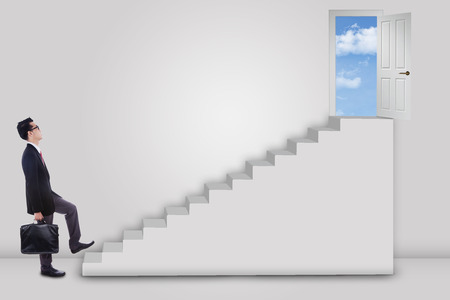 Businessman stepping up to the door on the sky with an arrow direction to the door photo