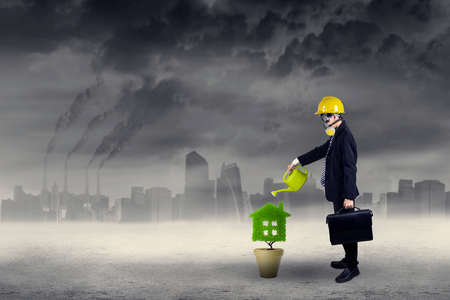 Businessman wearing a gas mask watering plant in pot with can. Shoot outdoors photo