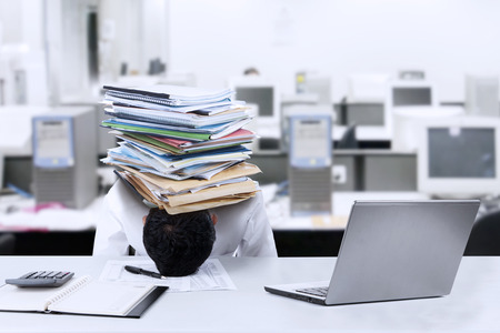 Depressed young businessman with a pile of documents on his head at office photo